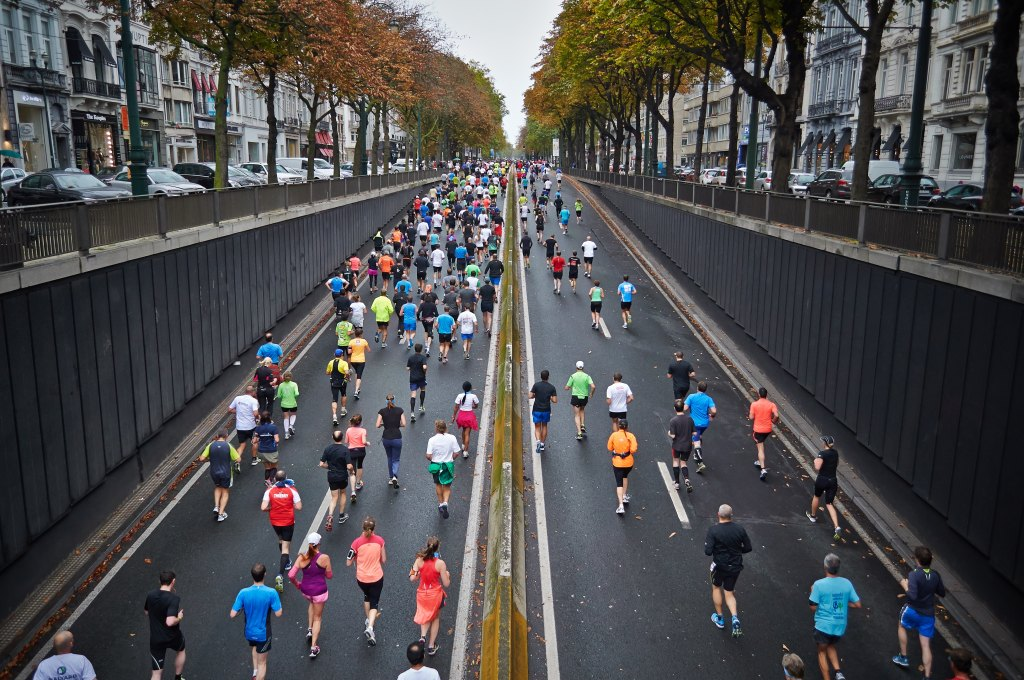 Large group of people running a marathon race on a city street