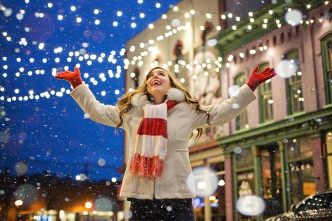 woman at winter event with Christmas lights above