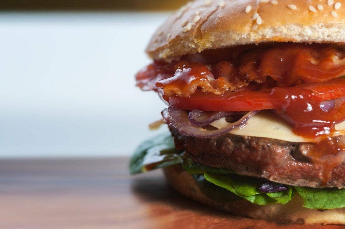 hamburger with bacon, lettuce, ketchup, and tomato