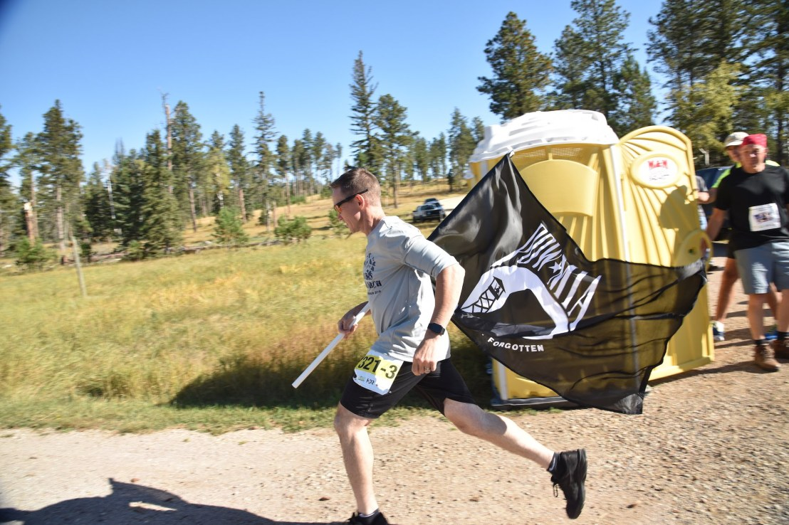 A Black Hills March and Marathon participant runs with a POW/MIA flag.