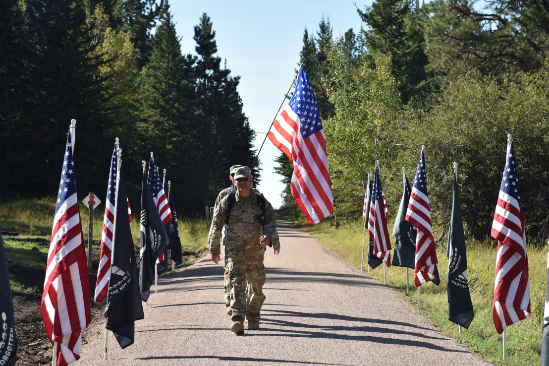 Two uniformed participants march through an array of flags while carrying one of their own.