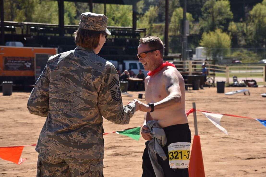 A participant wearing a branded bib is congratulated at the finish line.